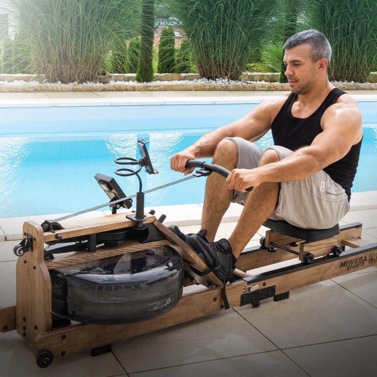 Wysportowany mężczyzna trenuje na maszynie do wiosłowania
