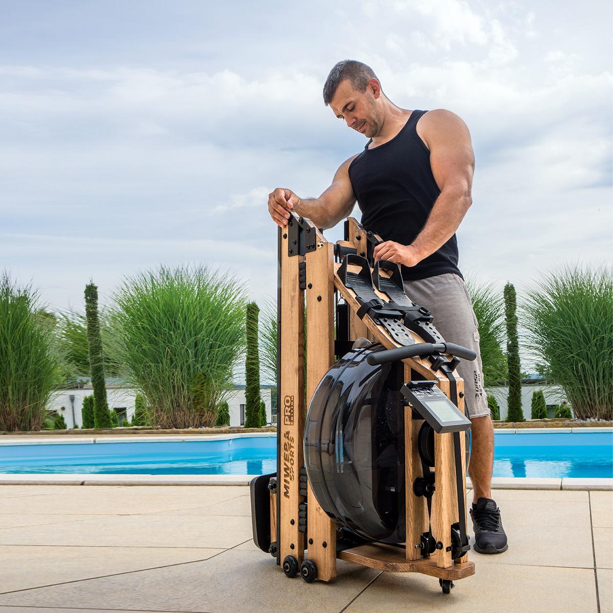 Sportowiec ze złożoną drewnianą maszyną do wiosłowania