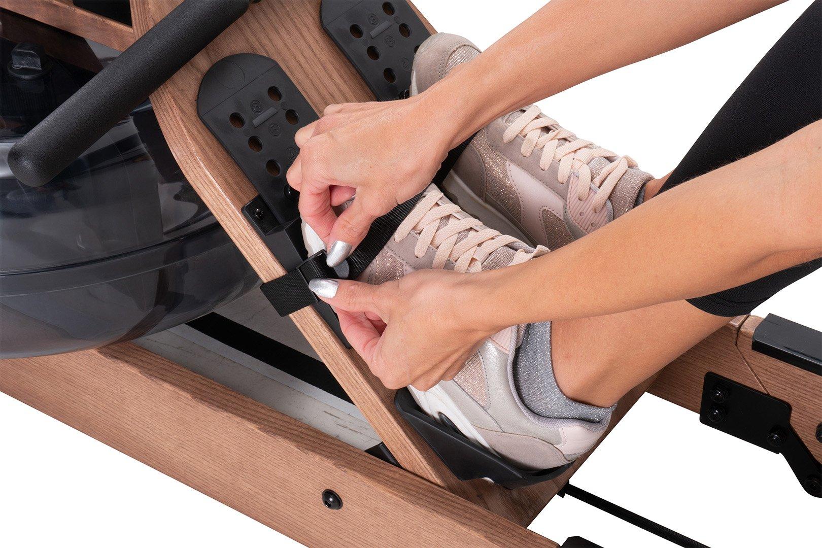 Sportsmenka zaciska stopę w pasach na stopy na maszynie do wiosłowania